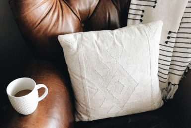 A leather chair with a white cup of coffee, white printed pillow and throw blanket