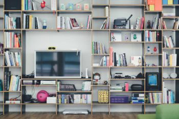 Shelving with books, video consoles and personal items on it with a tv
