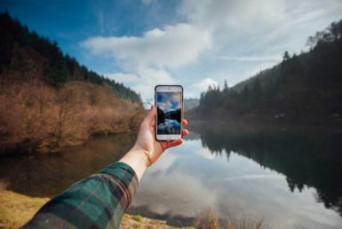 A view of a lake with mountains on both sides and a person holding a cell phone taking a picture of it.