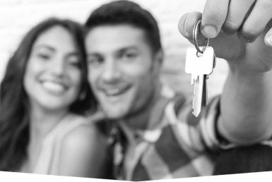 A women and man next to each other. The man is holding up a set of keys