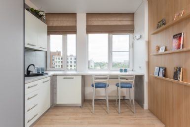 kitchen interior with counter with chairs near window and bookshelves